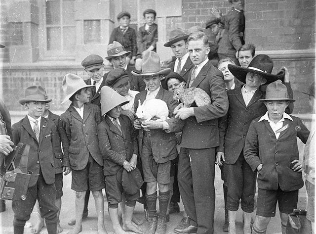 schoolboys being shown rabbits and hat 1927